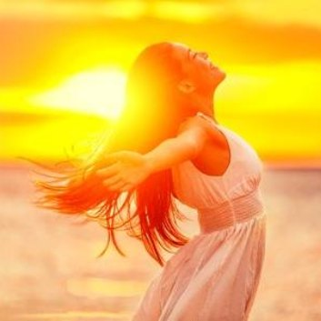 A happy and healthy woman with the Sun in the background.