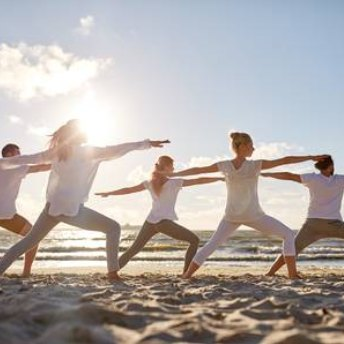 Group of happy people practicing yoga on a beach